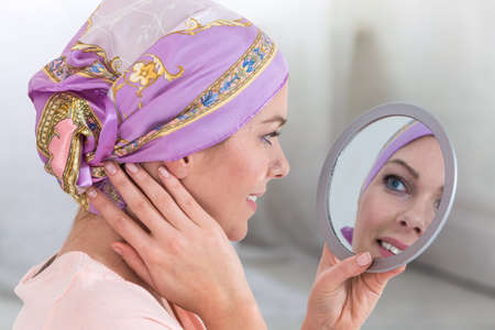 Beautiful breasts: woman adjusting her headscarf in a mirror