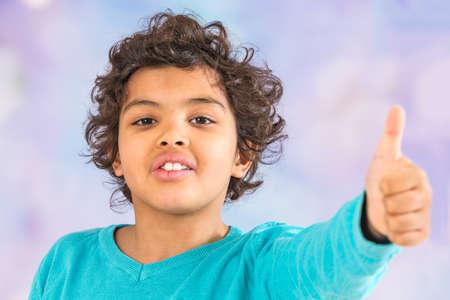 winning mood: young  boy is having his thumb up