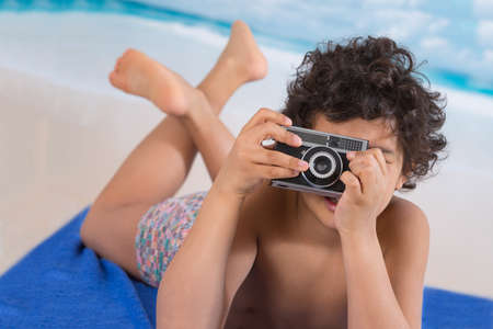 camra: Little boy using a vintage camra on the beach