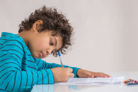 learning by doing: Boy concentrate in doing homework