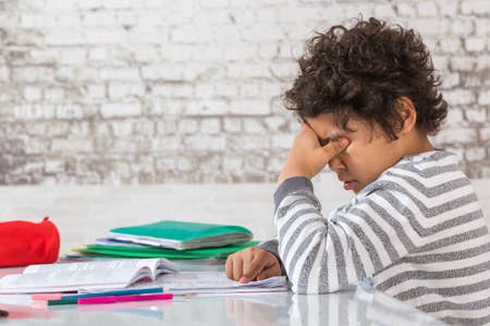 sad eyes: rubbing eyes boy  doing Homework Stock Photo