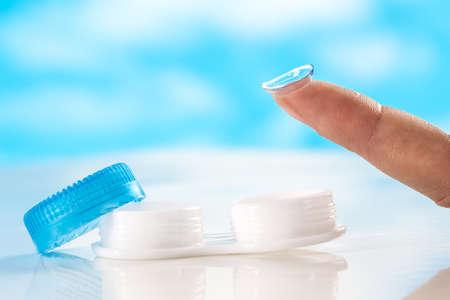 fermer lentilles de contact sur le doigt fond bleu Tipon Banque d'images