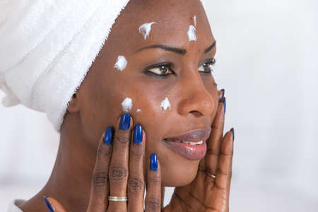 beautiful black woman: Portrait of beautiful young AfroAmerican woman wrapped in towel spreading cream on her face Stock Photo