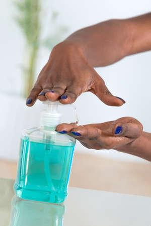 jabon: manos de la mujer africana que usa el desinfectante de manos higiénico Foto de archivo