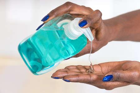 lavamanos: manos de la mujer africana que usa el desinfectante de manos higiénico Foto de archivo