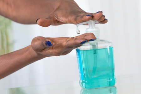 handwash: african womans hands using hygienic Hand sanitizer