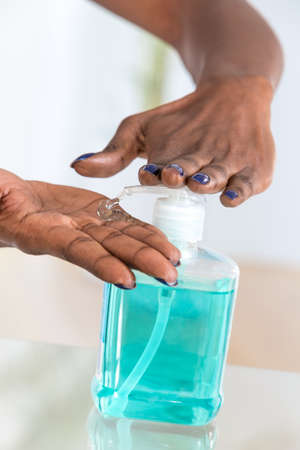 sanitizer: african womans hands using hygienic Hand sanitizer