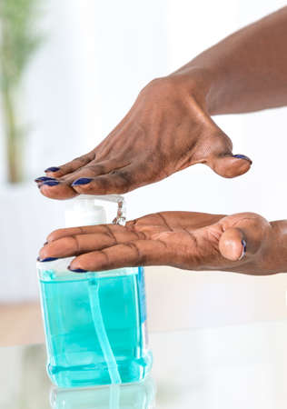 antibacterial soap: african womans hands using hygienic Hand sanitizer