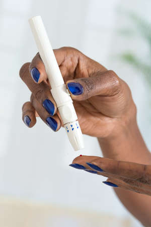 glucometer: Womans hands taking diabetes test with glucometer