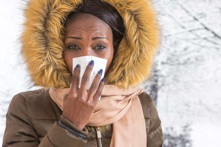 secretion: sick african  woman   blowing nose with tissue,  Flu season, vaccine