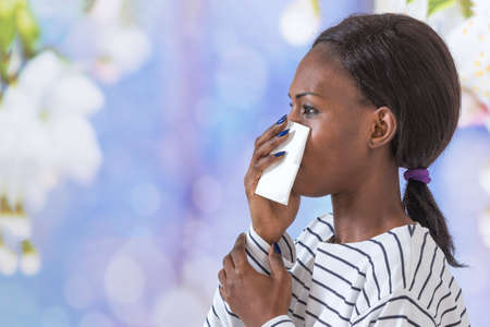 young black business woman blowing her nose