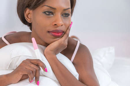 finding out: thoutgtfull woman finding out results of a pregancy test sitting on bed Stock Photo