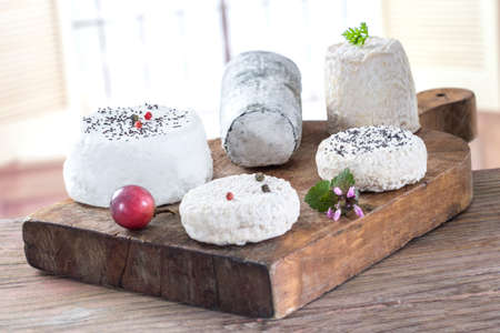 goat cheese: Various French  fresh goat cheese on wooden board Stock Photo