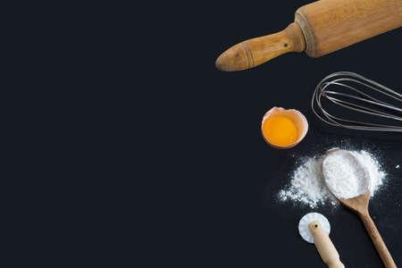 Rolling Pin, Schneebesen, Mehl und Eier auf schwarzem Hintergrund