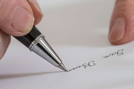 uncomplete: Hand of Woman Writing a letter on white paper