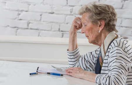 Senior donna che controlla pensione con calcolatrice a casa