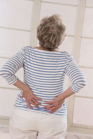 Back wiew of a Senior woman with back pain Stock Photo