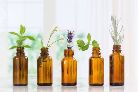 Bottle of essential oil with herbs and spices in brown bottles