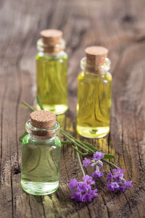 lavender oil: lavender oil in a glass bottle on a wooden background Stock Photo