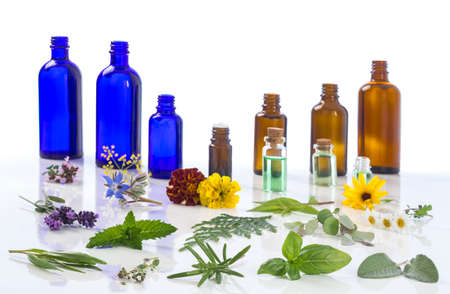 Medicinal plant and flower selection, with an aromatherapy essential oil glass bottle .