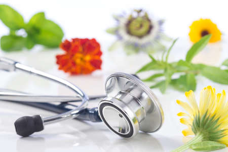 alternative therapies: Alternative medicine herbs and stethoscope on white background Stock Photo