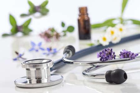 estetoscopio: Botella de aceite esencial con planta medicinal y estetoscopio en blanco