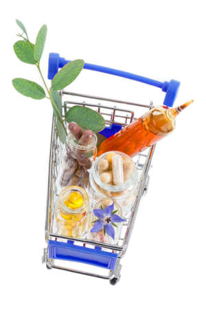 narcotism: Shopping cart full of pharmaceutical drug and medicine pills on white background