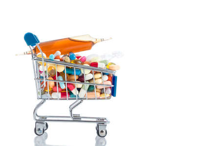 excess: Isolated shopping cart full of vitamin supplements on white backgrounds