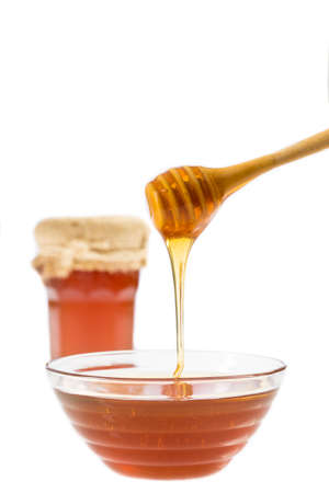 drizzler: honey pouring with wooden drizzler in a bowl