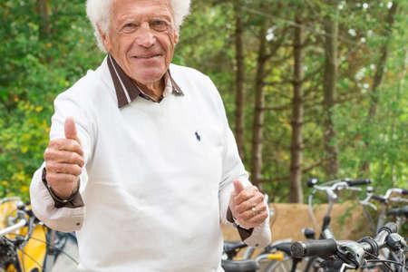 glücklichen älteren Mann mit einem Fahrrad in einem Park