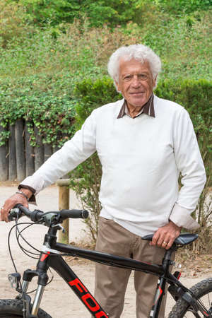 mann: happy senior mann with a bike in a park Stock Photo