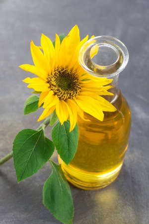 Jug sunflower oil with flower isolated on slate background