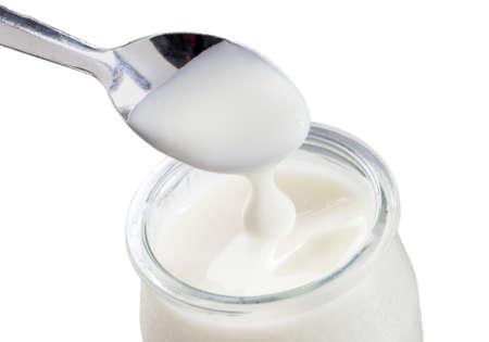 yogurt: bote de vidrio de yogur con cuchara aislada en el fondo blanco