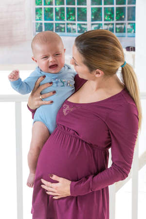 expectant arms: Young pregnant woman holding and looking at baby boy Stock Photo