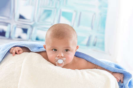 Cute baby with adorable face in bath towel after bath