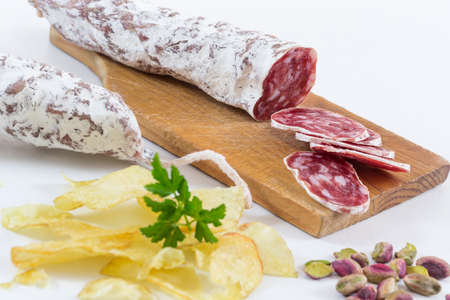 aperitive: wooden board with a knife cutting dried sausage for aperitive