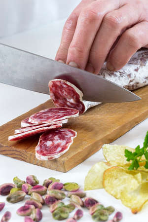 aperitive: Mans hand on the wooden board with a knife cutting dried sausage for aperitive