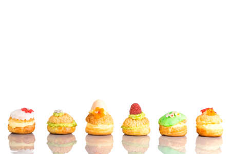Cream puff cakes or profiterole filled with whipped cream with fruit and decoration in line