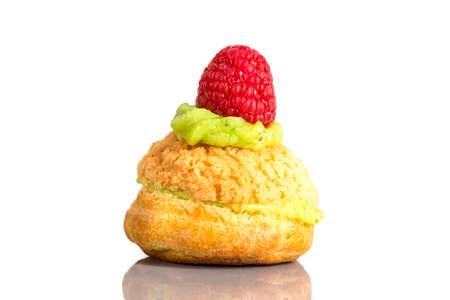 Cream puff cakes or profiterole filled with whipped pistachio cream served with stawberry decoration