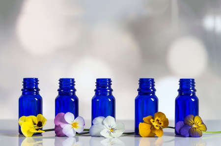 antirheumatic: Viola tricolor nice pansies,essential oil in bottle Stock Photo