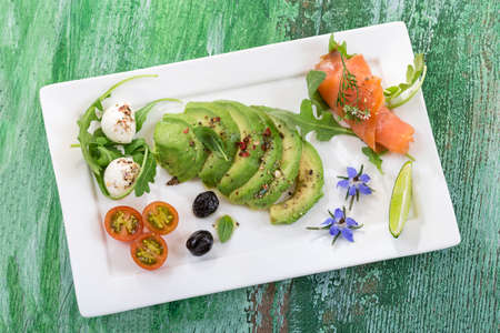 craked: Toasts with avocado and smoked salmon on the white plate on old wooden green craked board Stock Photo