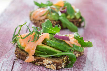 craked: Countrybread Avocado, salted salmon sandwich with fresh herbs on pink craked paintt wooden board background. Healthy eating theme