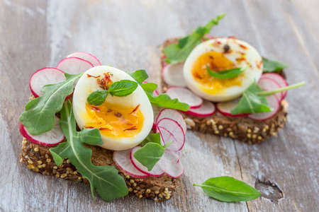 A hearty whole wheat sandwich with arugula, radishes and eggs