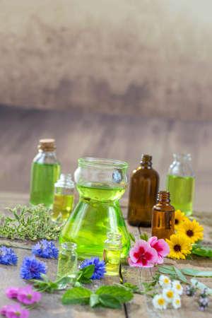 ハーブ療法と aromathrapy の概念: 木製の背景の花や新鮮な薬草で代替治療