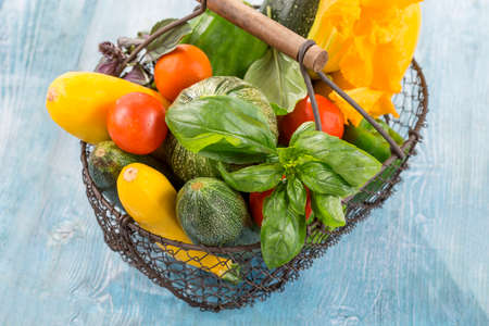 craked: Fresh vegetables on iron basket on old wooden paint board Stock Photo