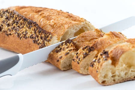 Closeup of a white baguette topped with different seeds, such as sesame and poppy seeds, sliced on a white background Foto de archivo