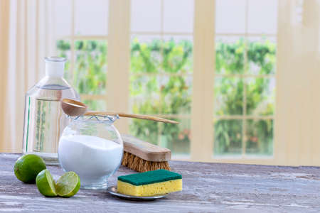 Eco-friendly natural cleaners baking soda, lemon and cloth on wooden table kitchen background,