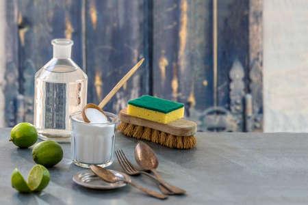 Milieuvriendelijke natuurlijke reinigingsmiddelen zuiveringszout, citroen en doek op de houten achtergrond van de lijstkeuken,