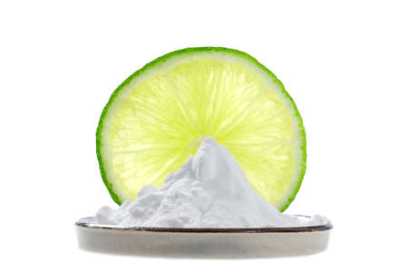 sodium bicarbonate in a cup with a fine slice of lemon and two whole lime behind Stock Photo