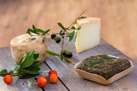 Corsican traditional various goat cheese with arbitys berry on wooden background